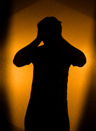 Depression and pain - silhouette of man in the darkness photo