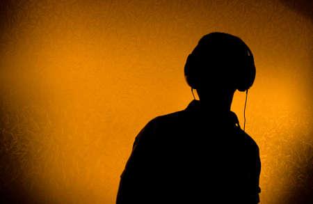 Silhouette of male DJ with earphones (back light)