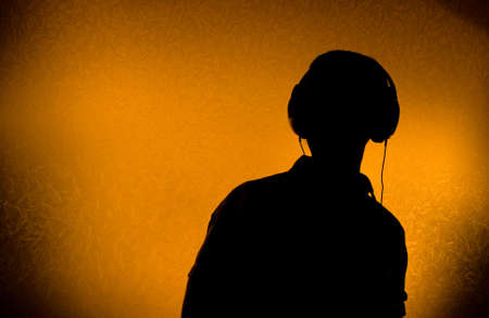 Silhouette of male DJ with earphones (back light)
