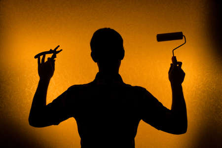 paintroller: Time for repair and Renovation. Back lit silhouette of man and paint-roller Stock Photo