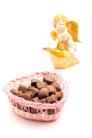 Sweet love - candies in wicker basket and angel on white photo