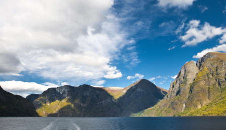 Mountains and norwegian fiord. Clouds and blue sky photo
