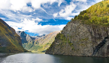 fiord: Mountains and Norwegian fiord. Blue sky with clouds