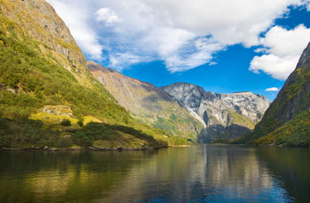 neroyfjord: Mountains and norwegian fjord in autumn. Clouds and blue sky