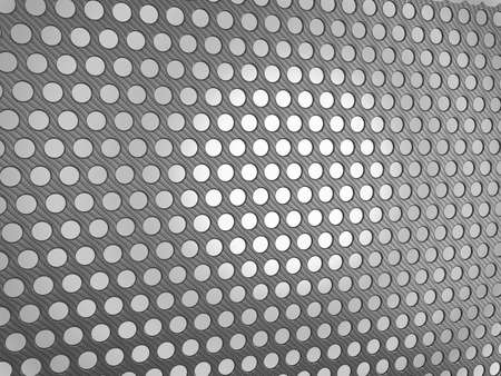 Carbon fibre surface with holes over studio light background photo
