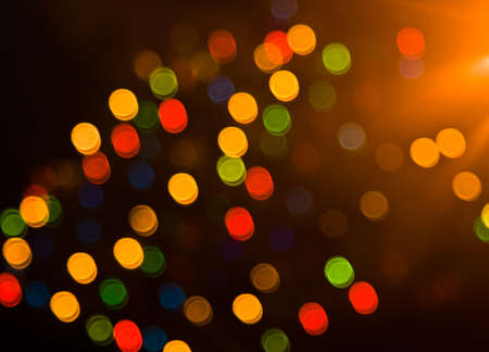 Blurred festive colorful lights over black useful as background photo