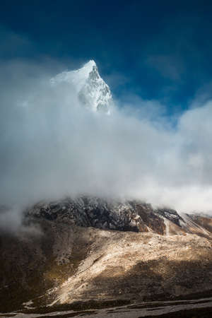 Blue Ridge Mountains: Cholatse 6335 m mountain summit hidden in clouds. Pictured in Nepal