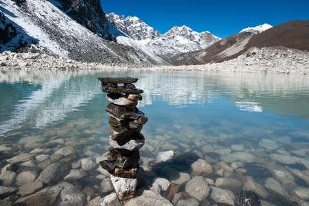 Harmony and balance: Stone stack and Sacred Lake near Gokyo. Travel to Nepal