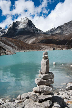 Harmony: Stone stack and Sacred Lake near Gokyo. Travel to Nepal Stock Photo