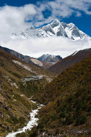Lhotse and Lhotse shar peaks. Village and stream in Himalayas. Pictured in Nepal photo
