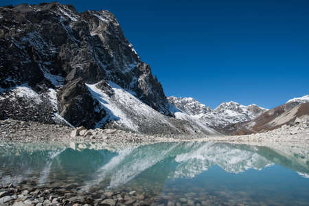 Mountain peaks and reflection in Sacred Gokyo Lake in Himalayas. Hiking in Nepal Stock Photo