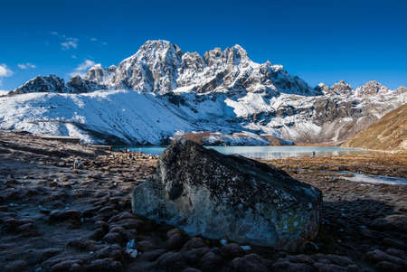 Sacred Gokyo Lake near village and mountain peaks in Himalayas. Travel to Nepal photo