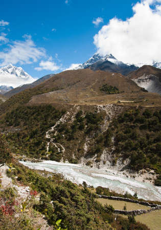 Himalayas: stream and Lhotse, Lhotse shar peaks. Pictured in Nepal  photo