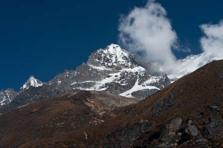 snowbound: Snowbound mountain peaks and clouds in Himalayas