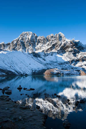 Mountains and reflection in Sacred Gokyo Lake in Himalayas. Travel to Nepal photo