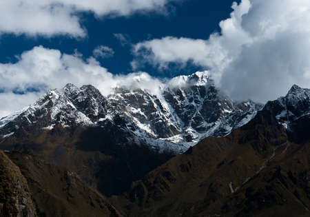 snowbound: Snowbound mountain peaks and clouds in Himalayas. Pictured in Nepal Stock Photo