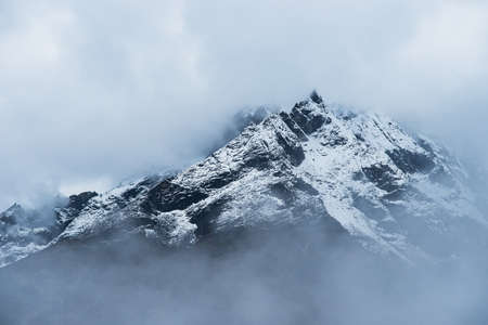 Snowed Mountain peaks hidden in clouds in Himalayas. Travel to Nepal