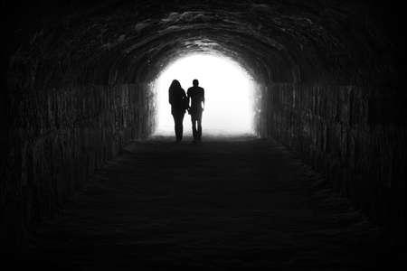 カップルとトンネルの希望と自由の終わりに光 写真素材