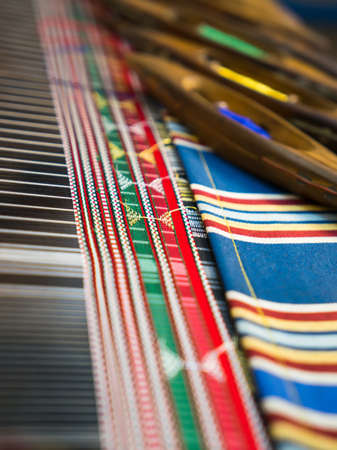 Weaving shuttles and colorful textile with pattern. Artistic shallow DOF photo