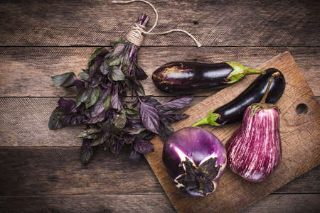 Aubergines and basil on chopping board and wooden table. Rustic style and autumn food photo photo