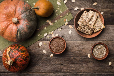 Rustic style autumn pumpkins with cookies and seeds on wood. Autumn Season food photo photo