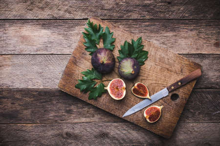 rustic style Cut figs with knife on chopping board and wooden table. Autumn season food photo photo