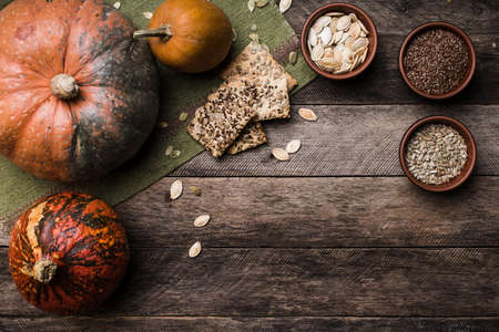 Rustic style pumpkins with seeds and cookies on wooden table. Autumn Season food photo