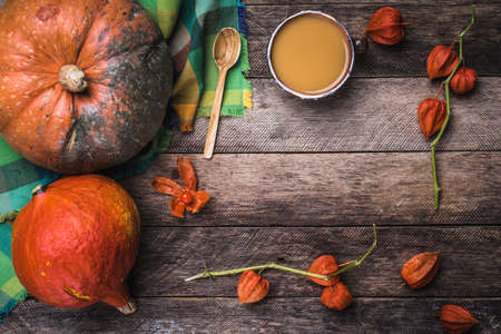 Rustic style pumpkins, soup and ground cherry branches on wood. Autumn Season food photo photo