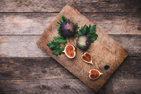 Figs on chopping board and wooden table. Autumn season food photo photo