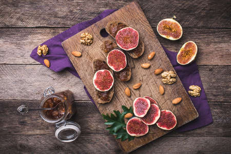 Sliced figs, nuts and bread with jam on choppingboard in rustic style. Autumn season food photo photo