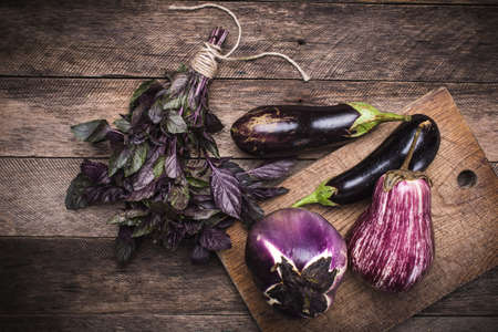 Aubergines and basil on chopping board in rustic style. autumn food photo photo
