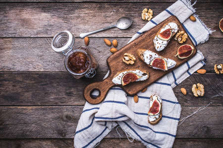 Bruschetta with figs and nuts on board in rustic style. Breakfast, lunch food photo photo