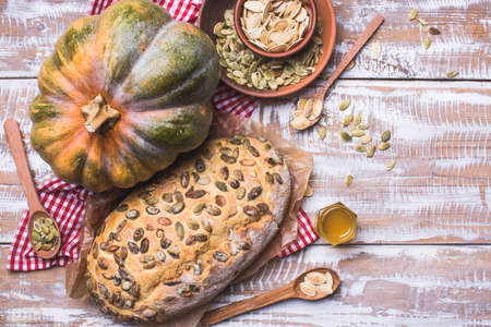 newly baked: Newly baked white bread with seeds and pumpkin on wood. Rustic style food photo Stock Photo
