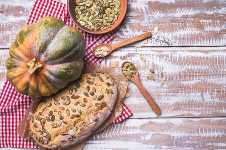 pain blanc: Le pain blanc avec des graines de citrouille sur table en bois. Style rustique
