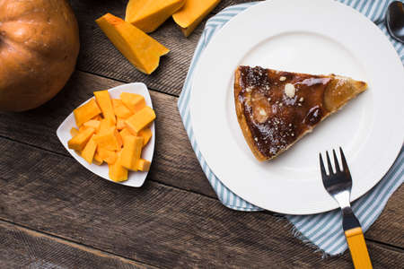 pie on plate and pieces of pumpkin in Rustic style. Food Photo photo