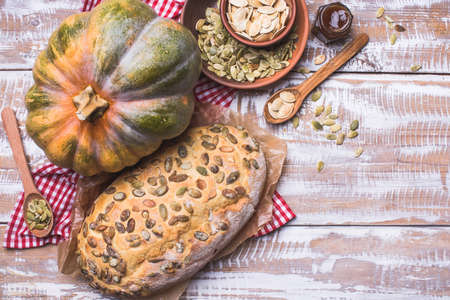 newly baked: Newly baked bread with pumpkin and seeds wooden table. Rustic style food photo Stock Photo