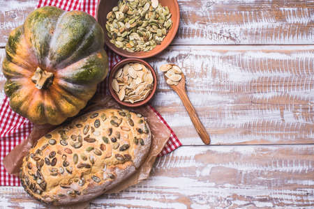 Newly baked bread with seeds and pumpkin on wooden table. Rustic style