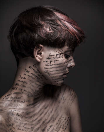Sad girl with writing and erased text on her body. Lonekiness and depression