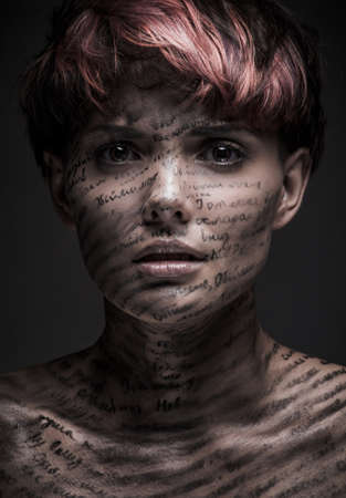 write writing: Portrait of scared or frightened girl with writing and erased text on her body