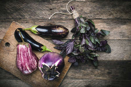 vegetarian food: Aubergines and basil on chopping board and wooden table. Rustic style and autumn food photo