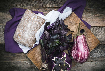 herfst eten: Aubergines basil and bread on chopping board and wood. Rustic style and autumn food photo