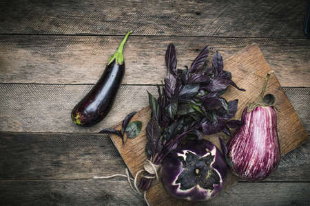 herfst eten: Aubergines and basil on chopping board and wooden table. Rustic style and autumn food photo