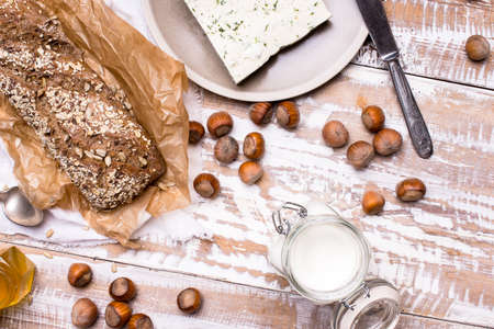 dill seed: Tasty Bread with seeds huzelnuts and cheese on board in rustic style
