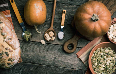 rustic food: Rustic pumpkins and bread with seeds on wood. Autumn Season food photo