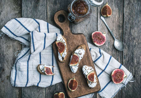 rustic food: Bruschetta snacks with jam and figs on napkin in rustic style. Breakfast, lunch food photo
