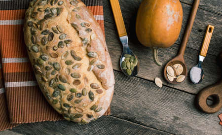 autumn food: pumpkin with bread and seeds on Rustic wood. Autumn Season food photo Stock Photo
