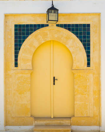Yellow door with ornament and lantern from Sidi Bou Said in Tunisia. Culture of Tunisia Stock Photo