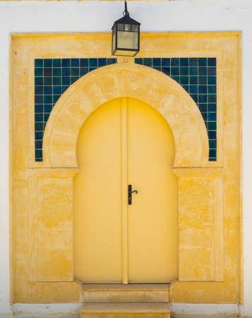 sidi bou said: Yellow door with ornament and lantern from Sidi Bou Said in Tunisia. Culture of Tunisia Stock Photo