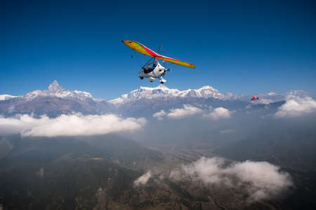 Ultralight trike and plane fly over Pokhara and Annapurna region. Machapuchare or fishtail and Himalayas on the background. Tourism in Nepal