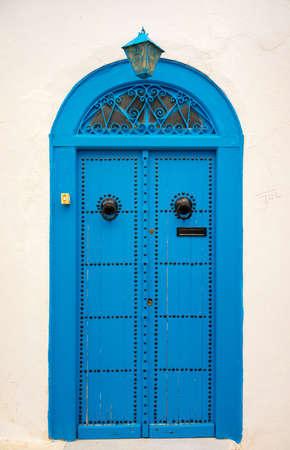 sidi bou said: Traditional blue door with ornament and lantern from Sidi Bou Said. Culture of Tunisia Stock Photo
